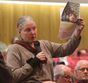 Marilyn Hunt holds up a picture of a flaming gas well at a public meeting (click to enlarge)
