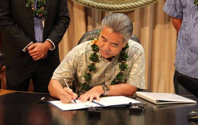 Hawaii Governor David Ige signs a bill that requires the state's power grid to deliver 100% renewable energy by 2045
