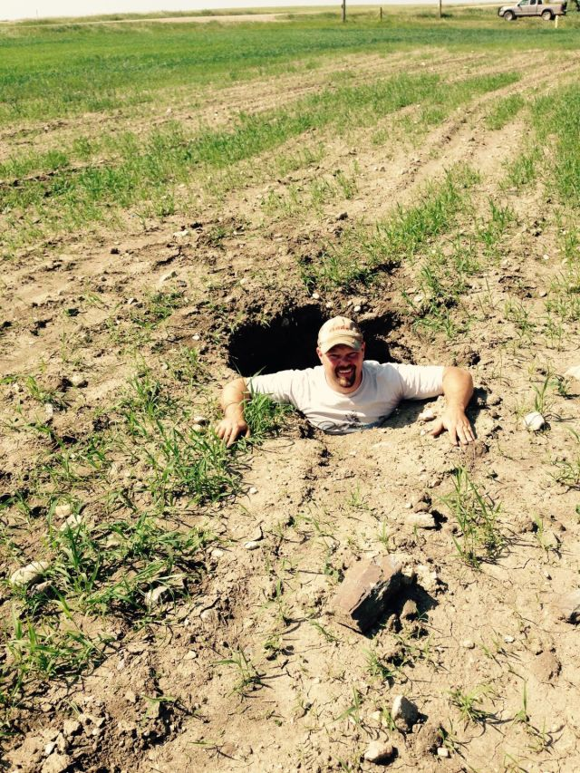 "Dennis Johnsrud's son standing in a hole that's opened up in a field where a pipeline was put in. ""They always say, we'll pack the trench,"" Johnsrud said, shaking his head,. ""I don't think so."""