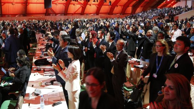 Delegates applaud as the agreement is announced. Photo: Getty images