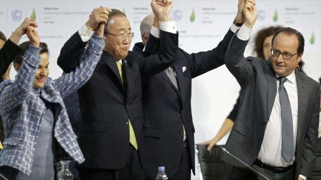 United Nations Secretary-General Ban-Ki Moon, French President Hollande and delegates raise their arms in triumph. Photo: Reuters