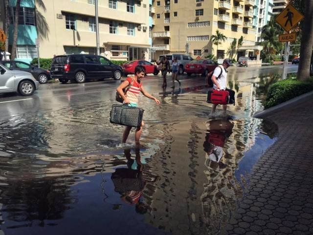 Tourists navigate the flooded streets of Miami during a king tide in 2015. Climatologists say these king tides will be normal high tides soon. Photo Emily Michot, Miami Herald